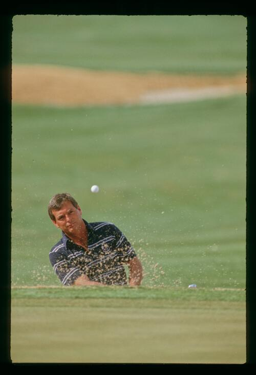 Fuzzy Zoeller splashing out of a greenside bunker at the 1987 Phoenix Open