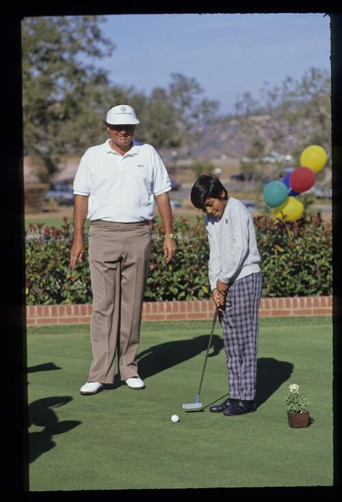 Raymond Floyd and a young fan on the putting green at the 1990 Ronald McDonald Children's Charity tournament