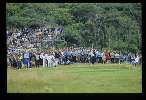 Nick Faldo hitting a tee shot at the 1987 Open Championship with Nick Price and Raymond Floyd looking on