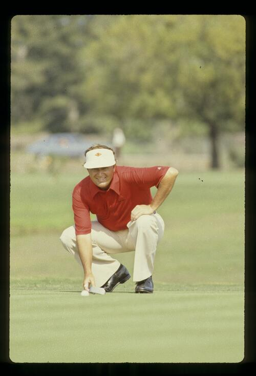 Raymond Floyd crouching behind the line of a putt during the 1981 American Motors Inverrary Classic