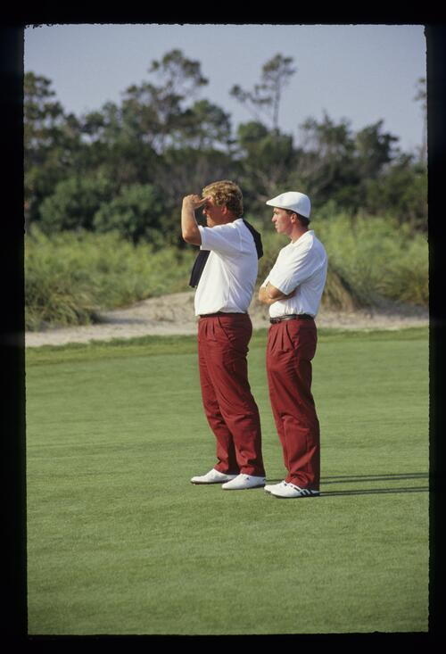 Colin Montgomerie shielding his eyes and David Gilford crossing his arms while they wait on the fairway during the first day foursomes of the 1991 Ryder Cup