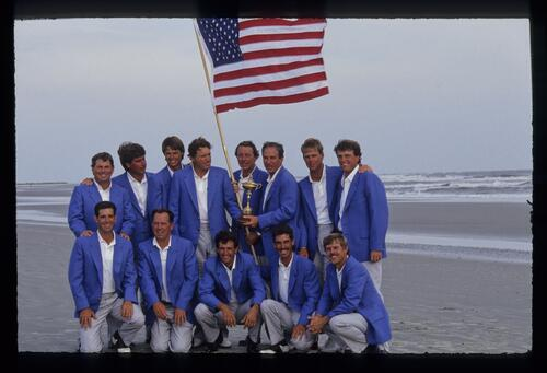 A victorious American Ryder Cup team pose with a stars and stripes flag on the shore at Kiawah