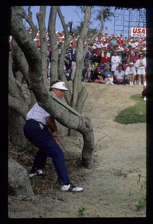 American Lanny Wadkins using his putter left handed from a tricky spot in the waste-ground at the 1991 Ryder Cup