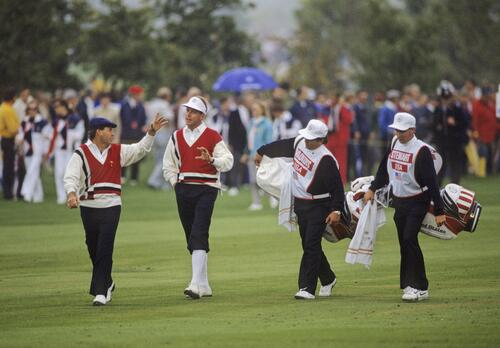 American teammates Lanny Wadkins and Payne Stewart discuss strategy as they walk the fairway at the Ryder Cup