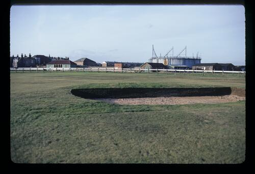 The ninth hole, 'Gas' with redundant gas works at the oldest golf course in the world, Musselburgh Links