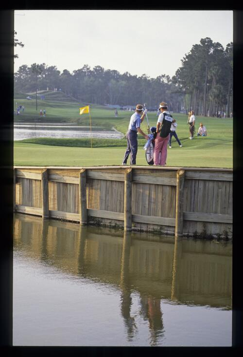 Tom Kite and his caddie are reflected in the pond adjacent to the 16th green during the 1989 TPC