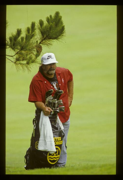 A caddie leaning on the bag during the 1987 US Open