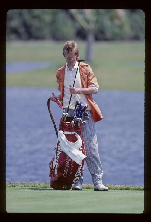 A caddie replacing a putter in the bag during the 1987 Chrysler Cup
