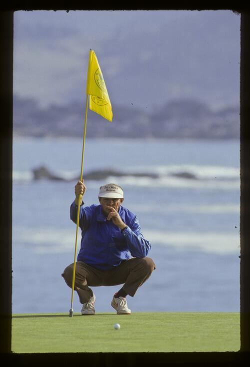 A caddie lining up a putt during the 1987 AT&T