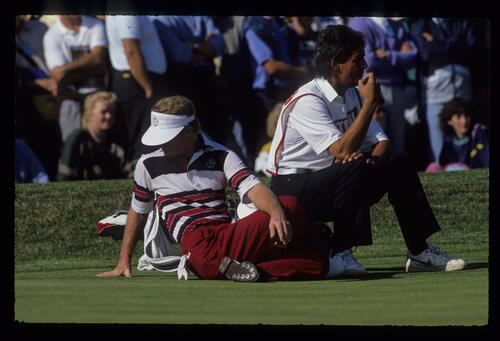 Tom Kite sitting on the floor and stretching as his pensive caddie sits on his golf bag at the 1989 Ryder Cup