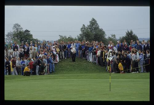The gallery has parted to allow Tom Kite sight of the green as he hits sand wedge from the rough at the 1989 Ryder Cup