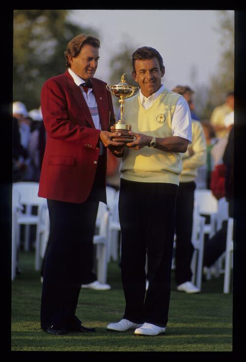 With the match halved at 14-14 Raymond Floyd and Tony Jacklin both hold the Ryder Cup trophy in 1989