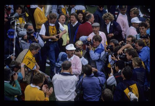 Sam Torrance and child are surrounded by photographers and cheering fans at the 1989 Ryder Cup while father, Bob Torrance, Mark James and Gordon Brand Jr mingle in the background