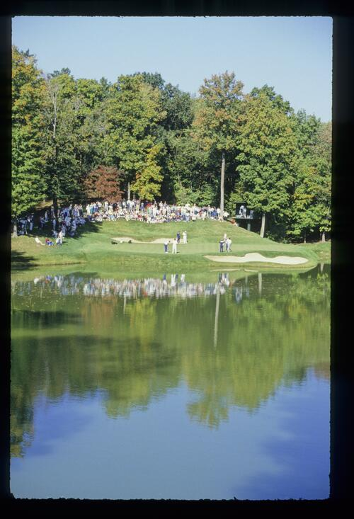 The action is reflected in a perfectly calm pond during the 1987 Ryder Cup