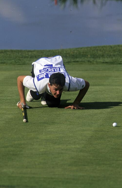 Gordon Brand Jr's caddie getting low to check the line of a putt at the 1989 Ryder Cup