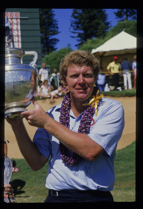 Andy Bean holding the 1986 Kapalua International Trophy aloft