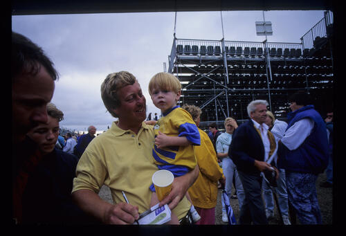 Howard Clark signing autographs with toddler in arms during the 1993 Open Championship