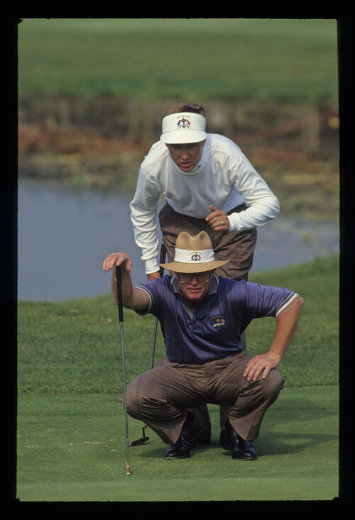 Davis Love III adds his opinion to that of Tom Kite as they line up a putt during the 1993 Ryder Cup