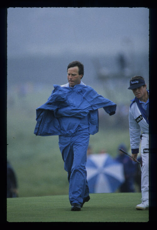 Ben Crenshaw shielding himself from the elements during the 1987 Open Championship