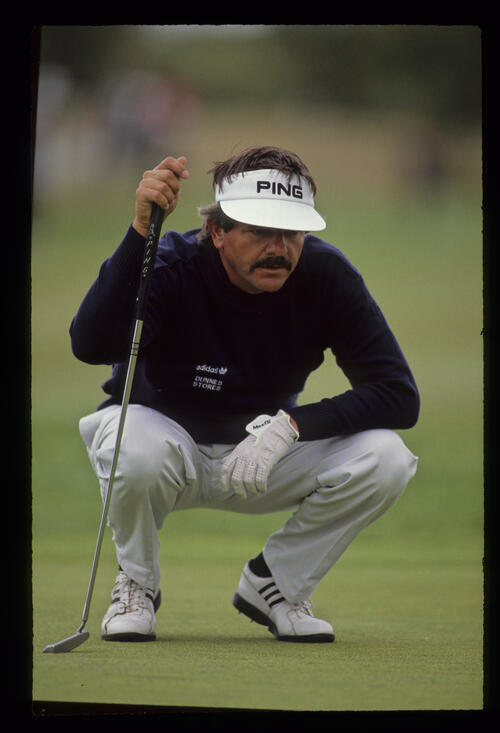 Rodger Davis squatting behind the line of a putt during the 1990 English Open