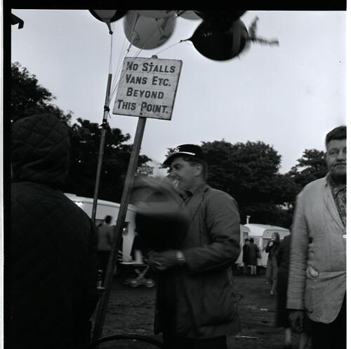 [An unidentified man next to a sign]