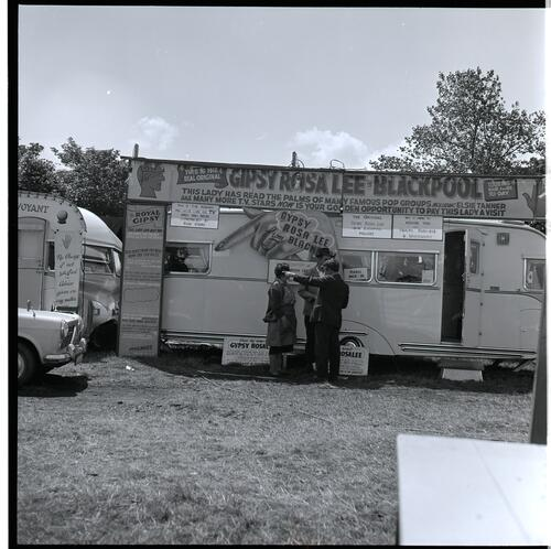 [Three unidentified people standing in front of a fortune tellers caravan]