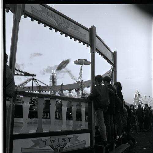 [A group of unidentified young men and women watching a carnival ride]