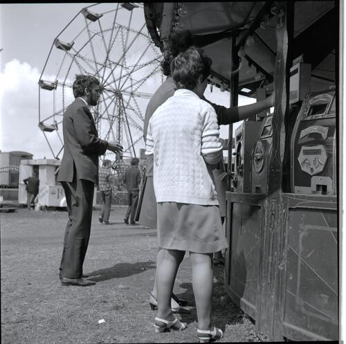 [An unidentified young man and woman playing a carnival game]