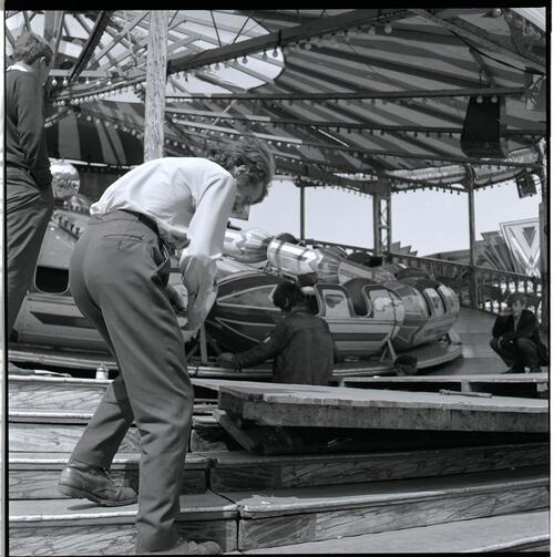 [Two unidentified men working on a carnival ride]