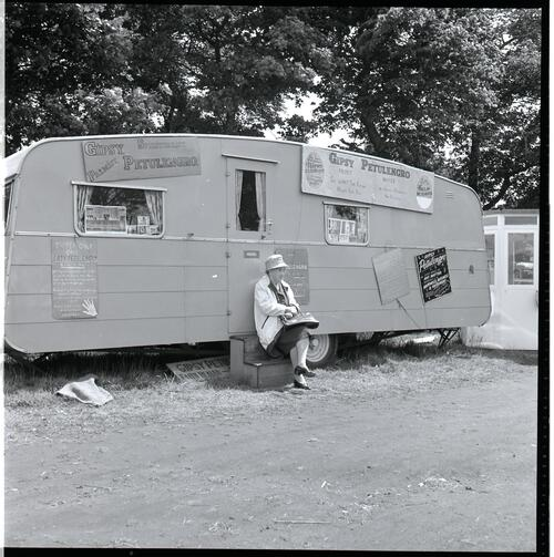[An unidentified woman sitting on a step in front of a fortune tellers caravan]