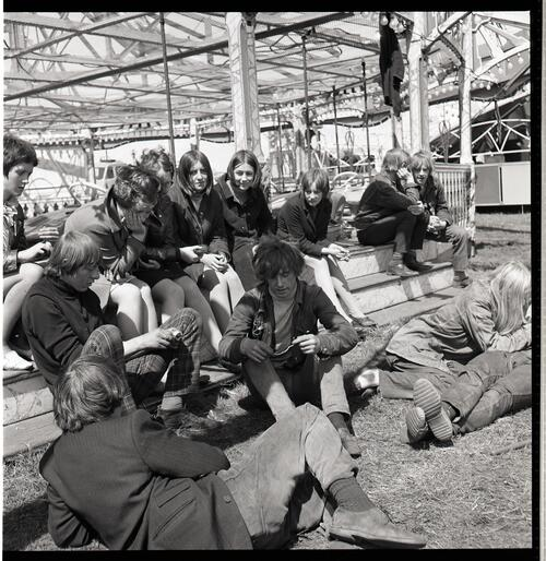 [A group of unidentified young men and women sitting in front of a carnival ride]