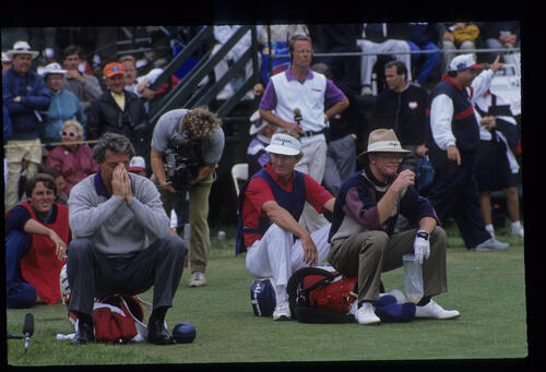 Hale Irwin and Tom Kite looking bored sitting on their golf bags during the 1992 US Open