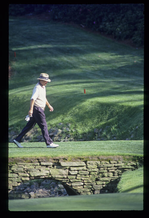 Raymond Floyd, with glove off, walks across a bridge to the green during the 1993 Masters