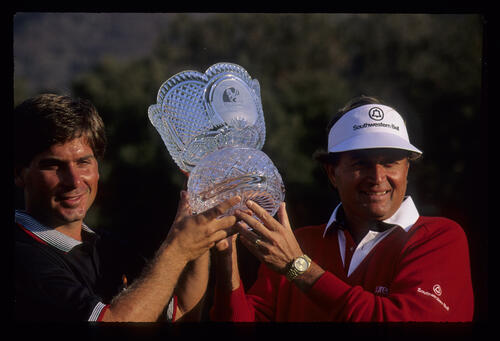 Teammates Raymond Floyd and Fred Couples; winners of the 1990 Ronald McDonald Children's Charity Tournament, hold the trophy aloft