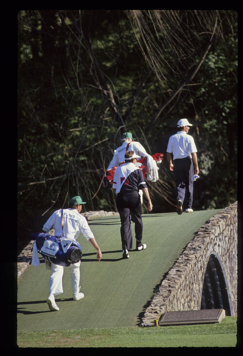 John Huston and Raymond Floyd cross the Hogan Bridge during the 1990 Masters