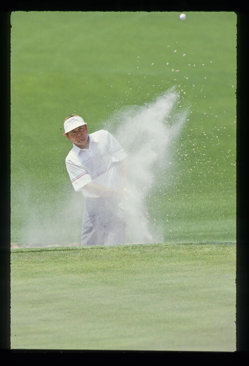 Sand obscures Raymond Floyd as he splashes from a bunker during the 1988 Masters