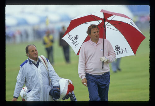 Raymond Floyd employs waterproof trousers and umbrella to ward off the rain during the 1987 Open Championship