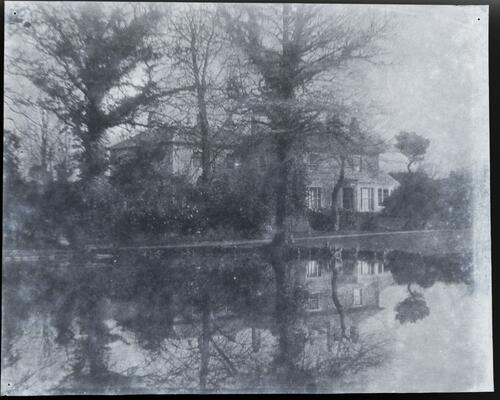 [Large house and leaf-less trees reflecting in a body of water]