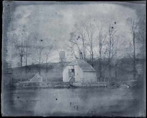 [Small barns or farm buildings next to a weir or dam, with leaf-less trees and a wind mill]
