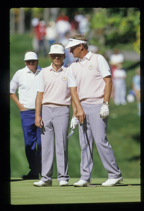 Bernhard Langer and Sandy Lyle conferring over a putt during the 1987 Ryder Cup with Lanny Wadkins in the background