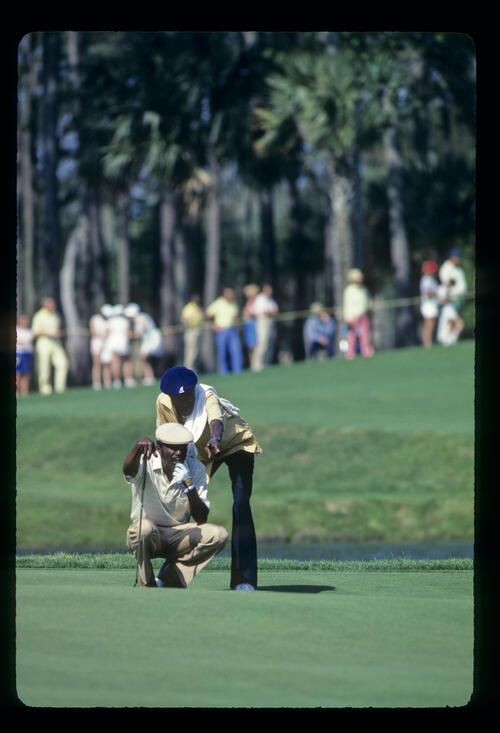 Calvin Peete and his caddie lining up a putt on his way to winning the 1985 TPC