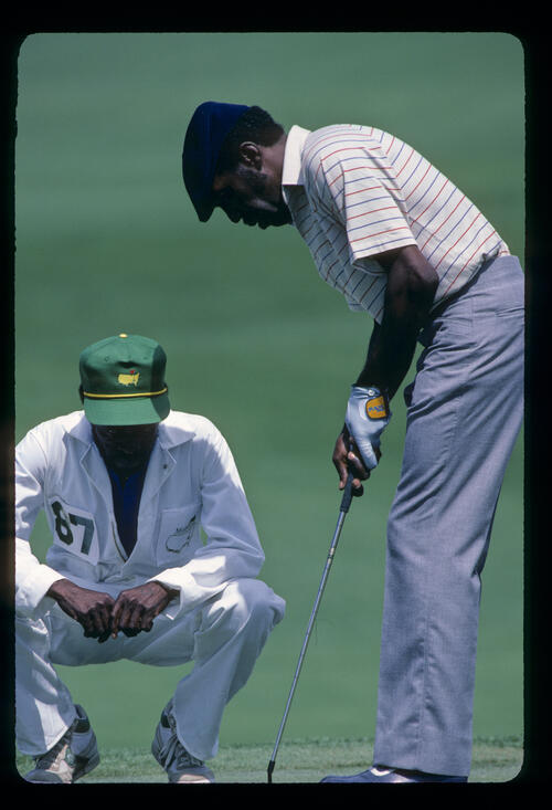 Calvin Peete and his caddie lining up a putt during the 1985 Masters
