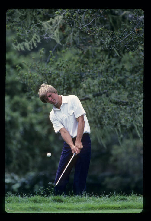 Bill Rogers chipping from the rough underneath trees during the 1982 Open Championship