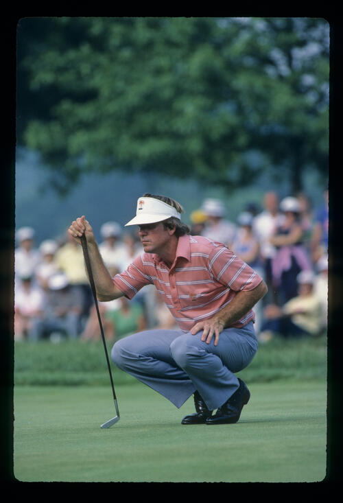 Bill Rogers squatting to line up a putt during the 1983 US Open