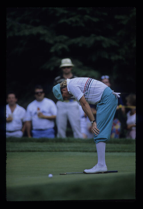Payne Stewart with dropped putter and hands on knees during the 1988 US Open