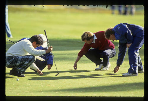 Jeff Sluman, Nobuo Seriwaza and their caddies clearing debris from the green during the 1988 Suntory World Matchplay