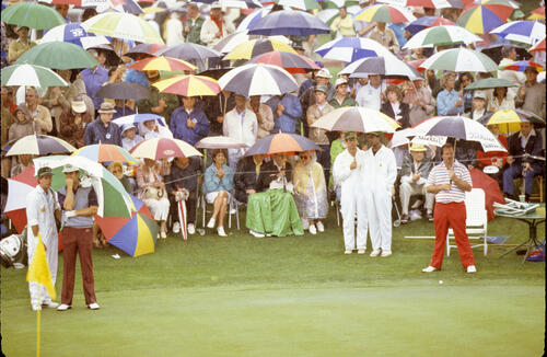 Craig Stadler sheltering from the pouring rain during the 1983 Masters