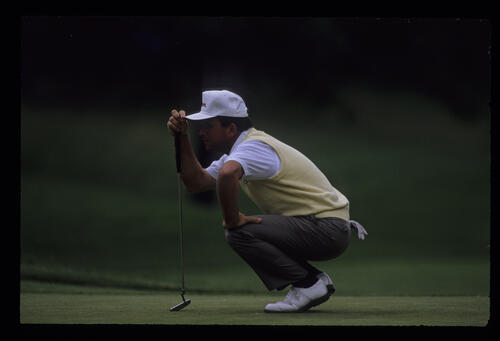 Hal Sutton squatting to line up a putt during the 1989 US Open