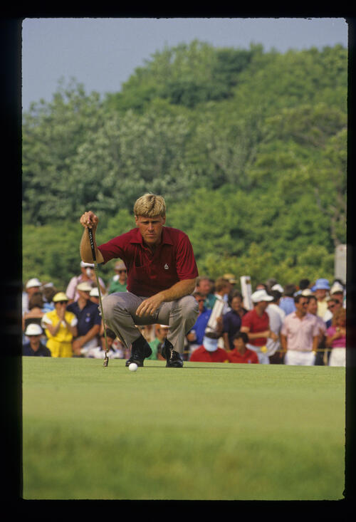 Hal Sutton squatting to line up a putt during the 1986 US Open