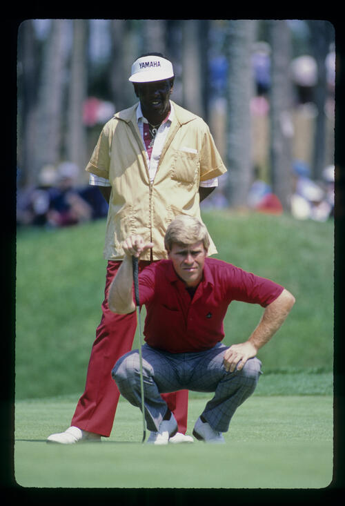 Hal Sutton and his caddie lining up a putt during the 1986 TPC